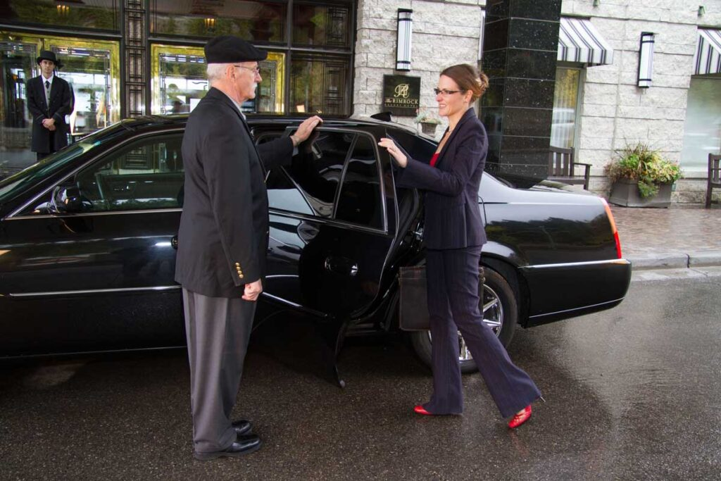 A happy customer enters her private transfer at the Banff Rimrock hotel