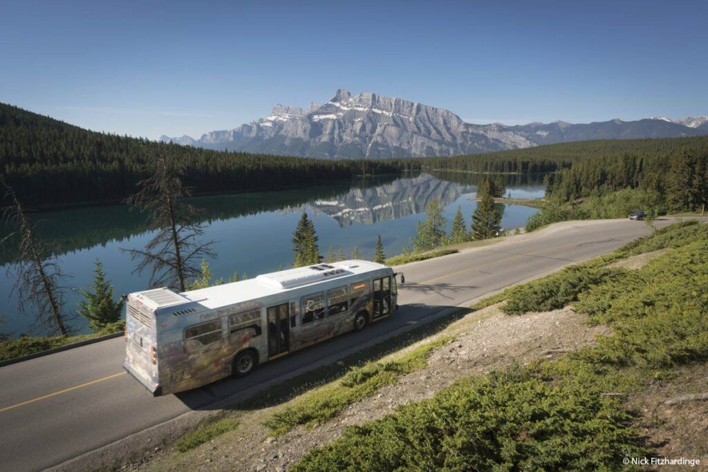 A Roam Transit bus passes Two Jack Lake in Banff National Parknnewanka