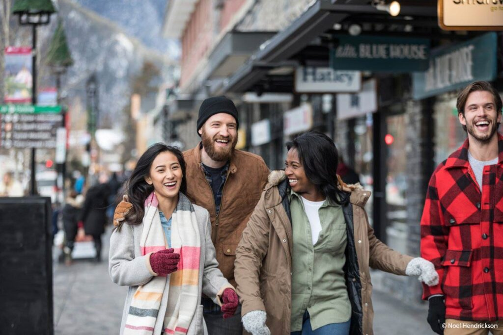 Getting Around Banff on foot - A group of friends walks along Banff Avenue