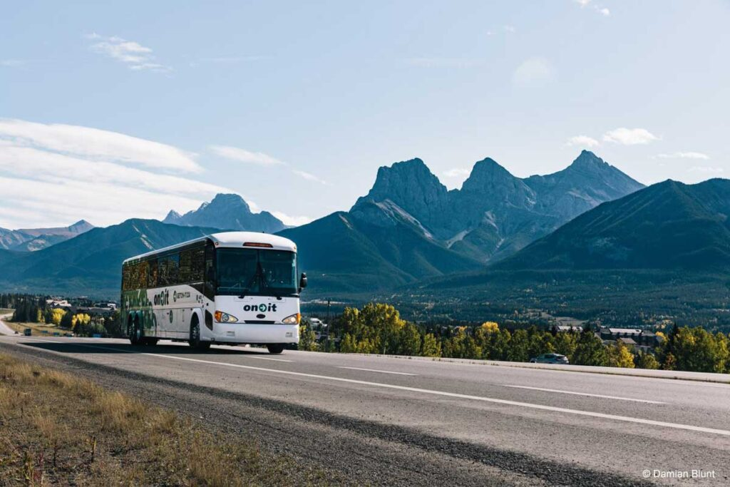 The On-It ublic transit bus passes the Three Sisters mountain on its way to Banff National Park