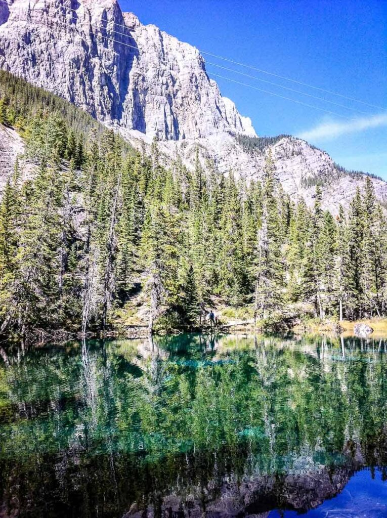 A reflection photograph of trees and mountains on Grassi Lakes near Banff National Park