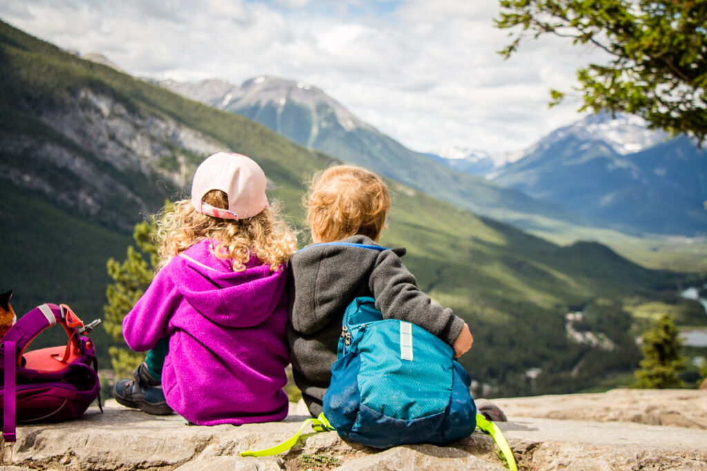 Two kids enjoying the view at the top of Tunnel Mountain - a popular kid-friendly hike in Banff National Park