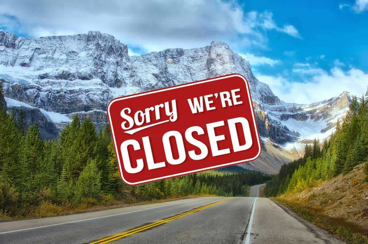 "A ""Sorry we're closed"" sign hangs in front of Banff National Park"