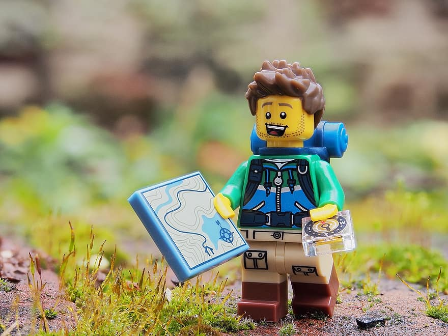Lego hiker with his hiking essrntials: a compass and map