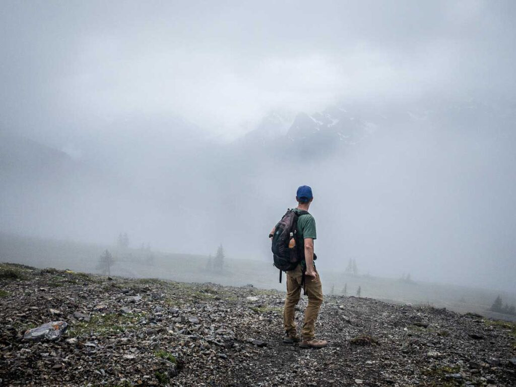 the mountains of the Spray Valley Provincial Park emerge through the clouds on the EORR hike near Banff National Park