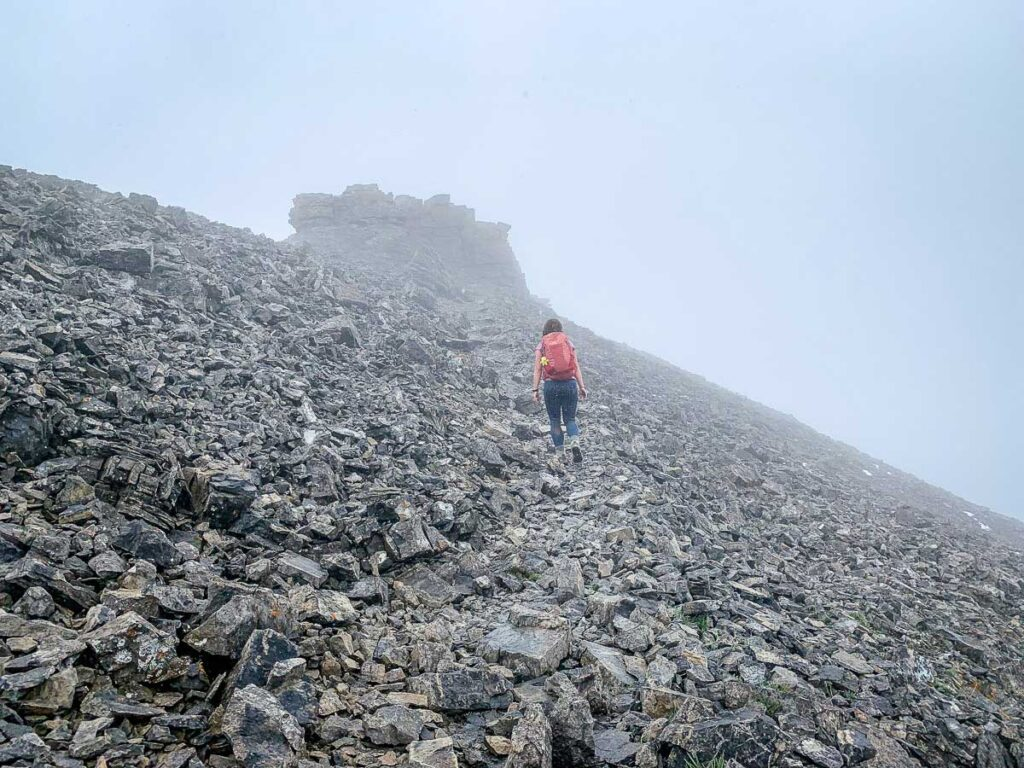 A female hiker nears the top of the East End of Rundle trail - a popular hike in Kananaskis near Canmore, Alberta