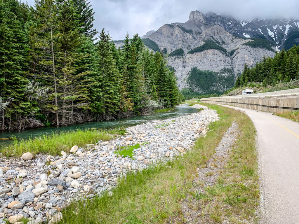 The Banff Legacy Trail passes a river with views of Cascade Mountain on the bike ride from Canmore to Banff