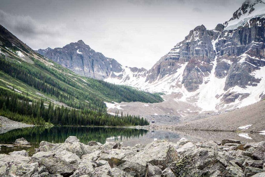 The Consolation Lakes hike is an easy walk through a beautiful forest to an alpine lake surrounded by Rocky Mountains