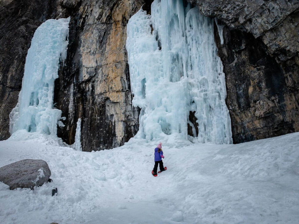 A girl on snowshoes walks under a frozen waterfall on the Grotto Canyon icewalk in Kananaskis County