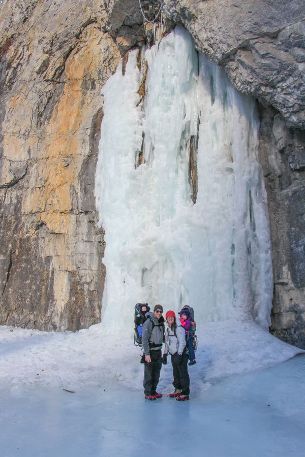 A family with a toddler and preschooler stand in front of a frozen waterfall on the Grotto Canyon ice walk near Banff, Canada
