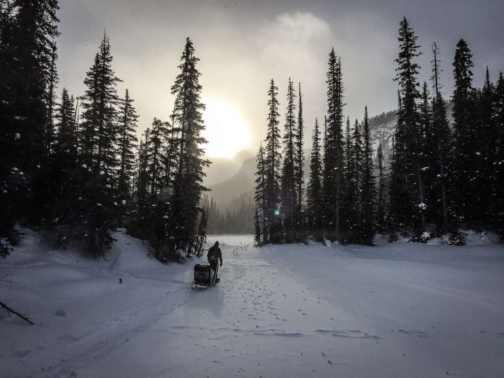 A father snowshoeing on the Kananaskis Hogarth Lakes trail pulls a baby in a Chariot with the ski attachment
