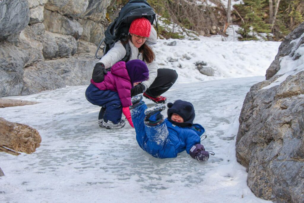 A toddler slides down the icy river while on the ice walk beneath Grotto Mountain near Canmore, Alberta