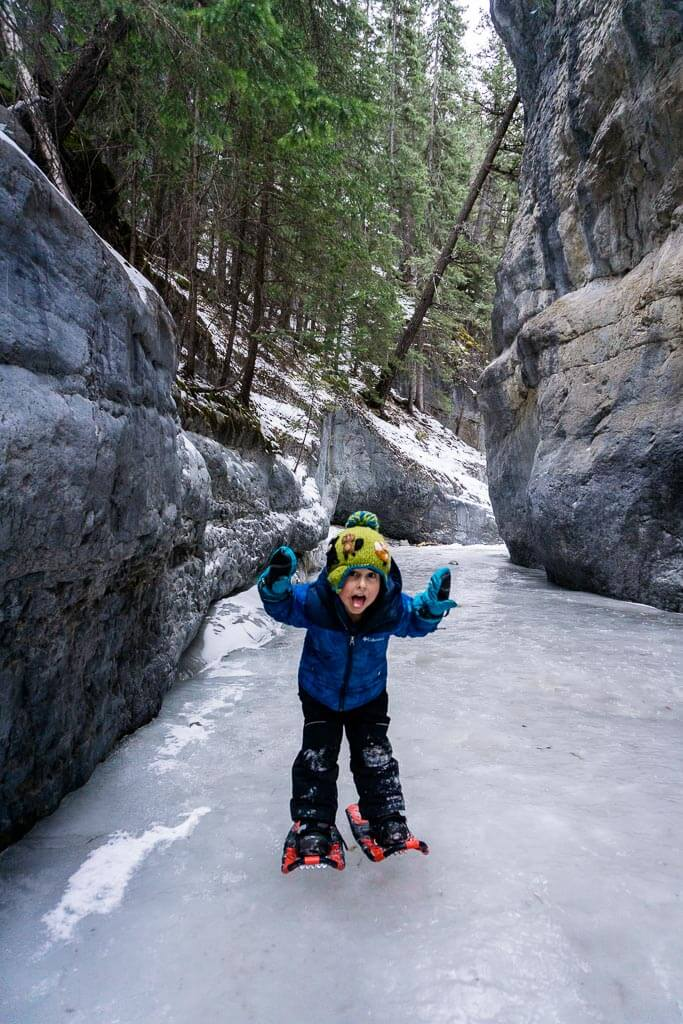A small boy wearing snowshoes hams it up while hiking the Grotto Canyon Trail in winter