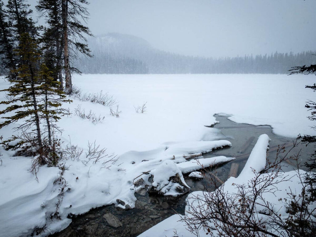 A snow-covered, nearly frozen Watridge Lake in Kananaskis Country, Alberta