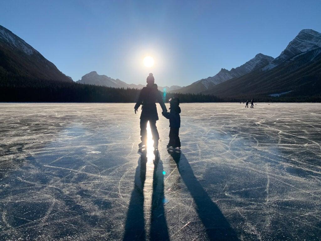 A family enjoys wild ice skating on Goat Pond in Kananaskis Country, Alberta