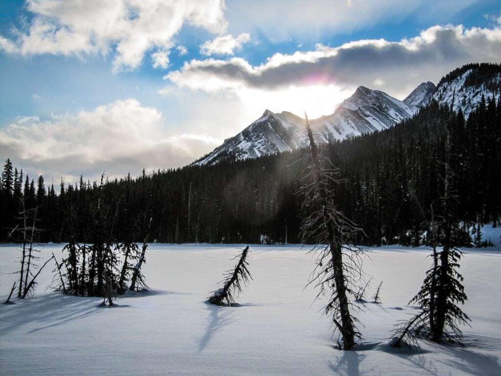 A beautiful sunburst behind a snow covered lake seen on the Hogarth Lakes trail in Kananaskis, Alberta