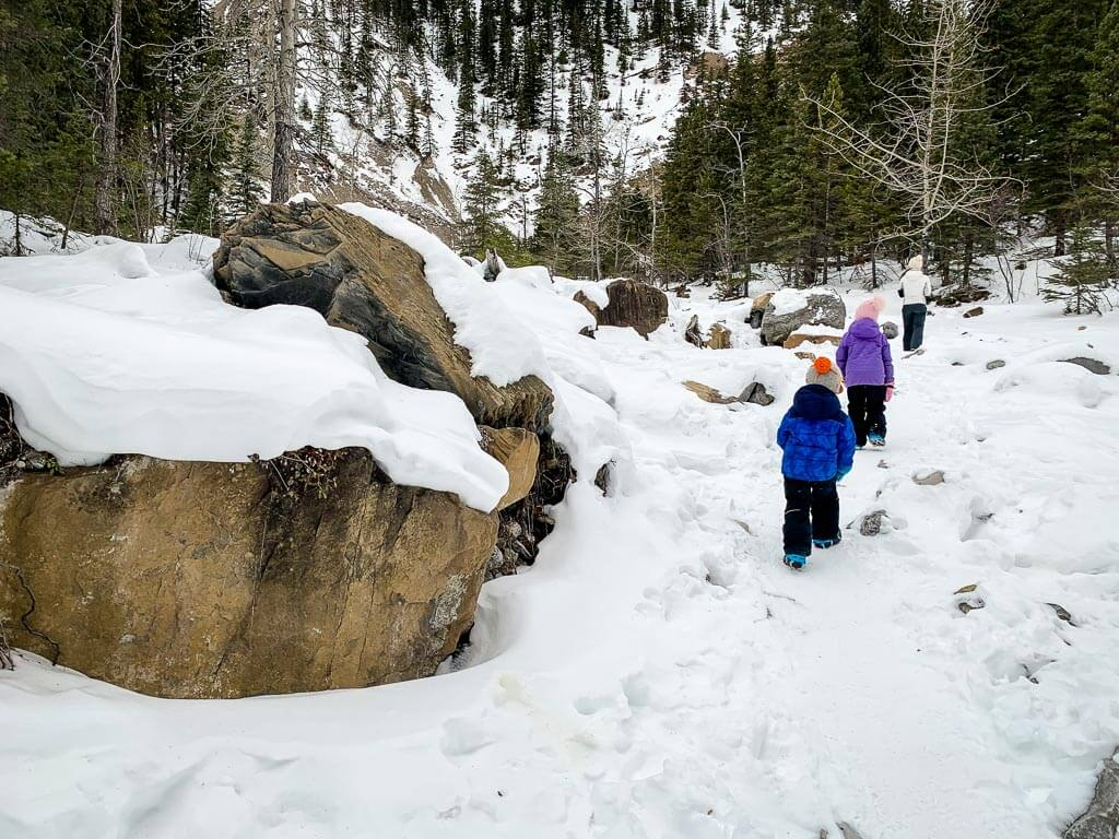 Our kids often wear a toque, winter jacket, snowpants, gloves, winter boots and traction devices while hiking in Kananaskis in winter