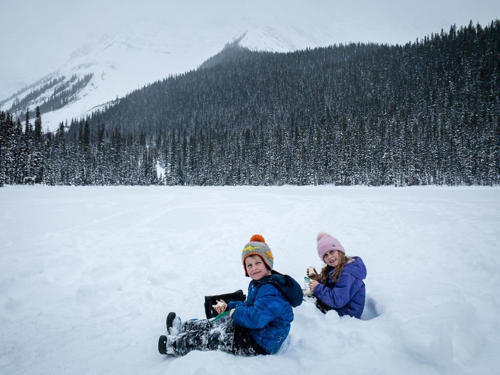 Kids eating lunch on a frozen Shark Lake beneath Mt. Shark in Peter Lougheed Provincial Park, Kananaskis