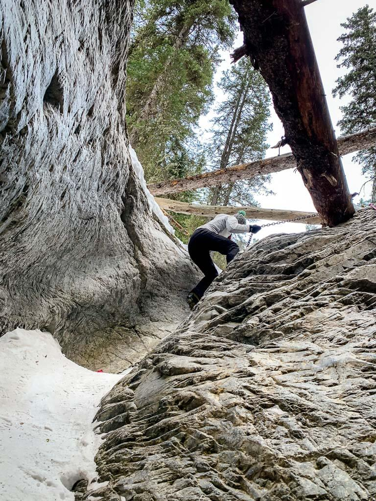 Using chain ropes to climb up the McGillivray slot canyon requires upper body strength