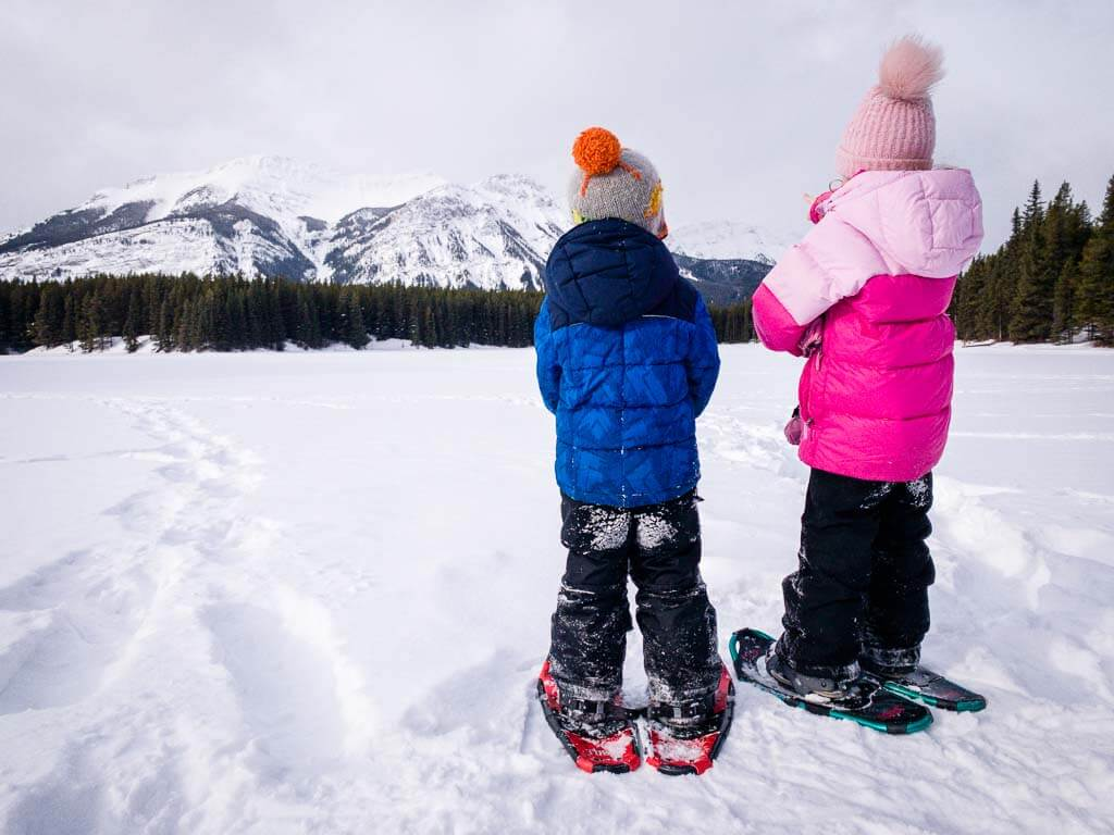 kids with snowshoes looking at mountain view across Marl Lake in Kananaskis