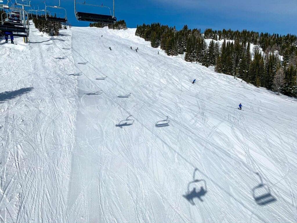 Shadows from the Wawa chairlift over the Wawa Bowl run at Sunshine ski resort in Banff, Canada