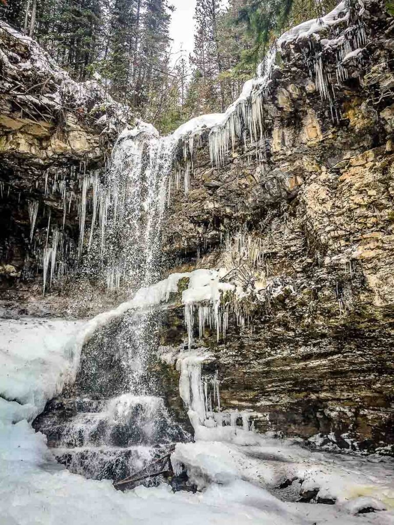 hiking Troll Falls in spring to see a partially frozen waterfall in Kananaskis Country