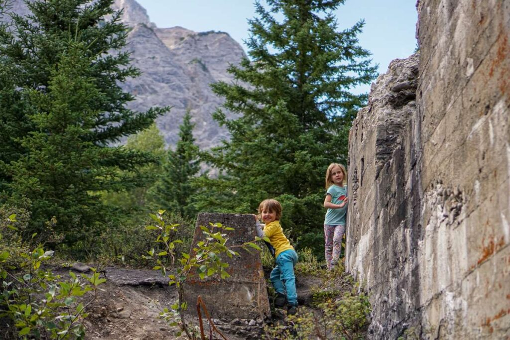 Kids exploring the foundations of the Tipple at the Bankhead coal mine ghost town in Banff, Alberta