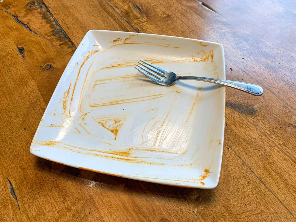 canmore takeout food - an empty butter chicken plate from Curry's Curries