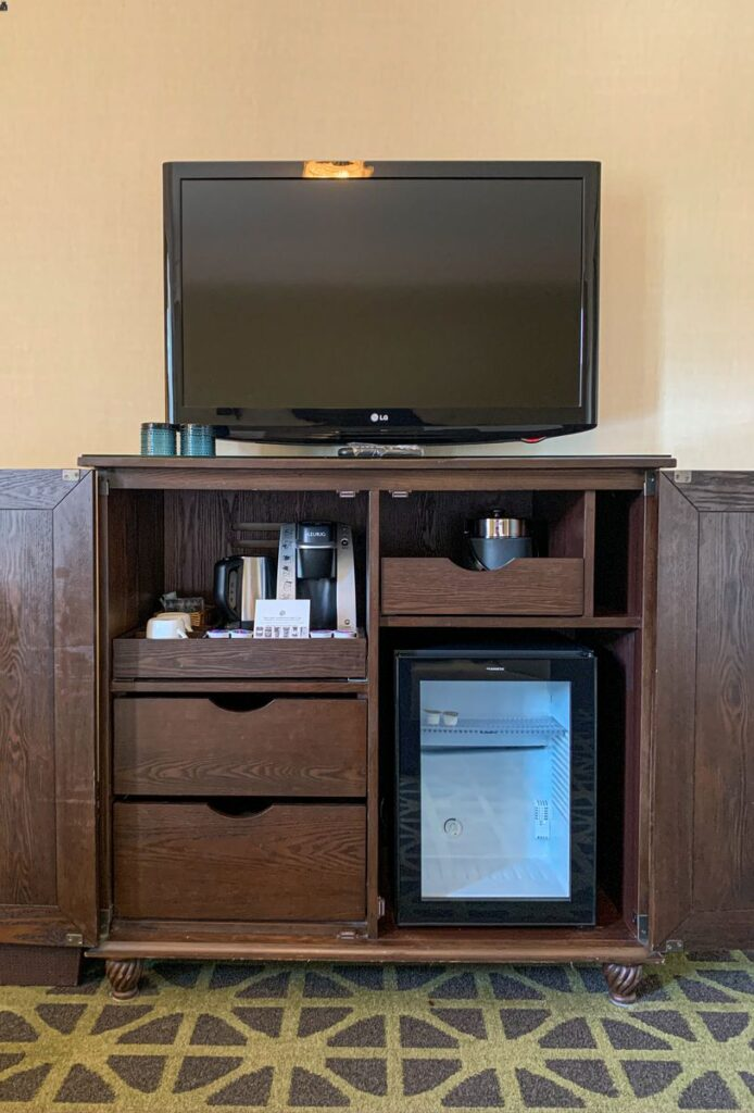 The TV, Keurig and mini-fridge in a Fairmont Room at the Banff Springs Hotel in Banff National Park, Canada