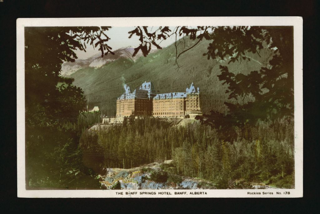 Hand-colored photograph of the Banff Springs Hotel with a panorama of the Rocky Mountains in the background. Hand-colored photograph by J. Fred Spalding 1943