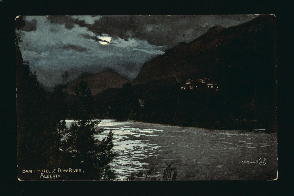 A picture of the Banff Springs Hotel and the Bow River at night under the stars and moon