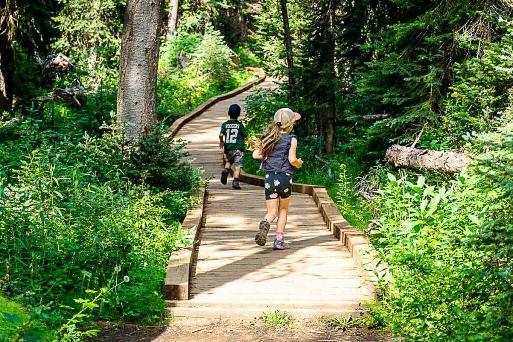 kids running on wooden boardwalk along Boom Lake hiking trail in Banff