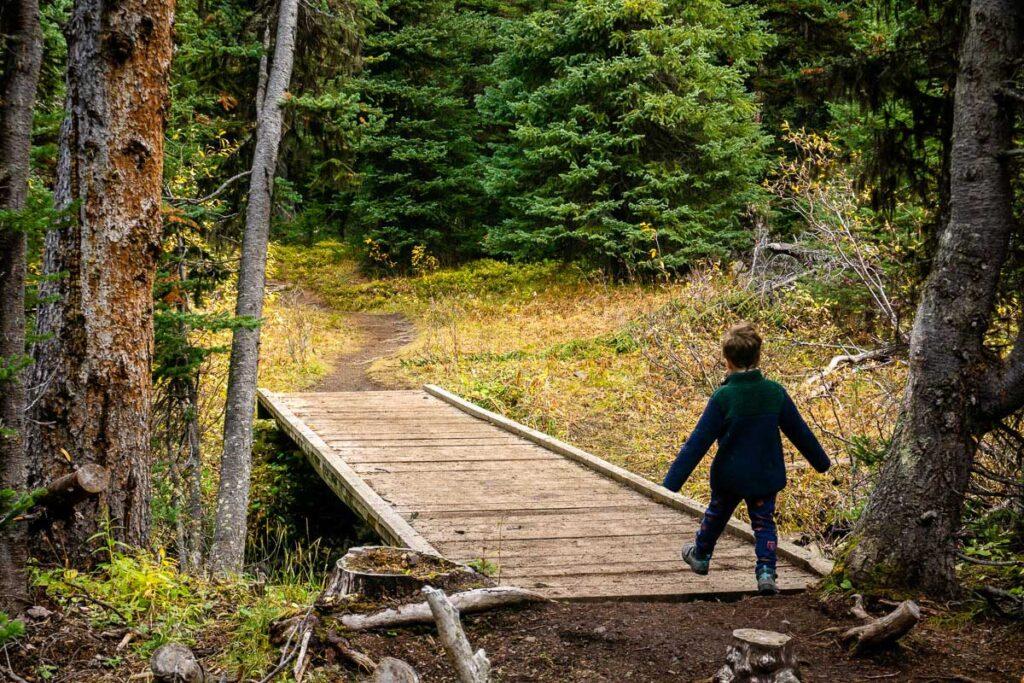 boy crossing bridge on Rummel Lake hiking trail