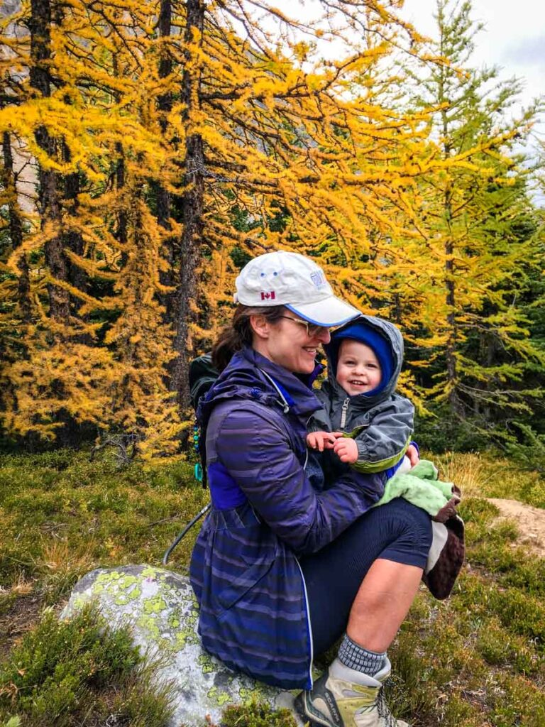 mother holding baby in front of golden larches on Kananaskis hike - Ptarmigan Cirque