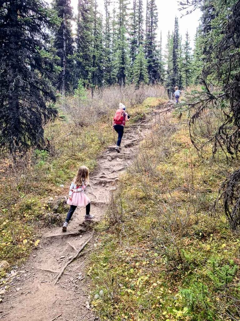 mother and children hiking up steep sections on Rummel Lake hiking trail in Kananaskis