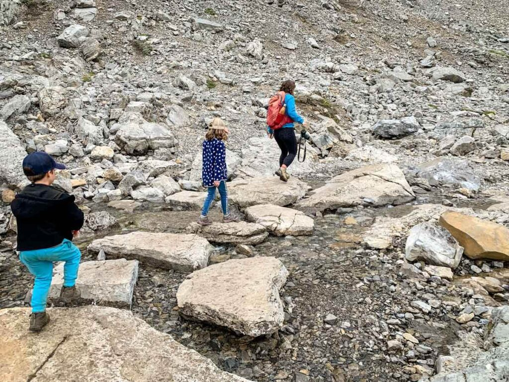 family hopping across rocks on Ptarmigan Cirque hiking trail in Kananaskis