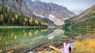 sitting at Taylor Lake with larches on the shore - best Banff Larch Hikes