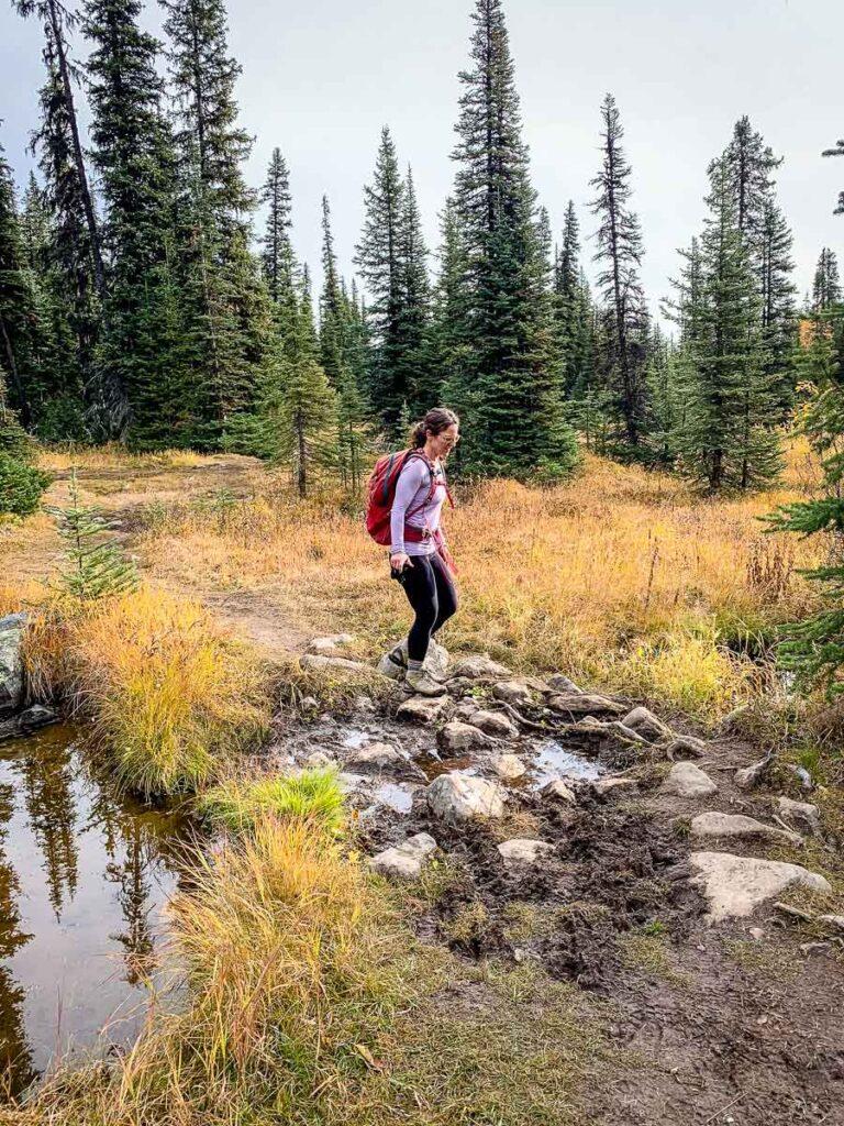 hopping across rocks to avoid mud along Taylor Lake hike in Banff