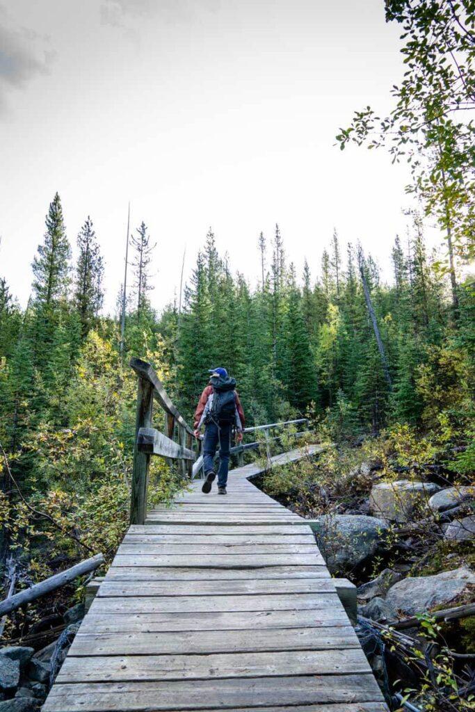Man walking over bridge on Arnica Lake hiking trail in Banff